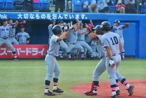 本塁打を放ちホームインする沓掛(写真中央)と盛り上がるベンチ